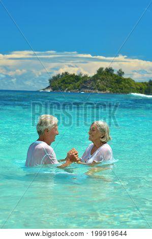 Portrait of elderly couple standing in sea water