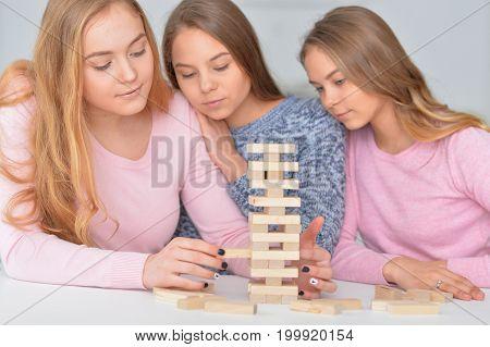 Three teenage girls playing with wooden blocks