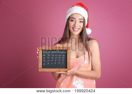 Young woman in Santa hat with chalkboard counting days until Christmas, on color background