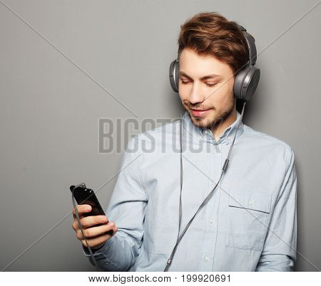 Handsome young man wearing headphones and holding mobile phone while standing against grey wall