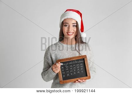 Young woman in Santa hat with chalkboard counting days until Christmas, on light background