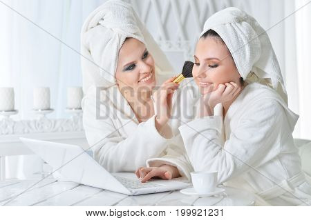 Two beautiful young women in bathrobes sitting at table with laptop