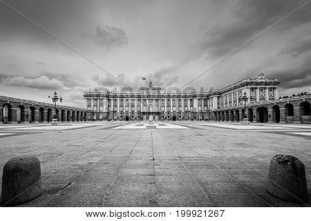 Madrid Spain - May 22 2014: Wide-angle view of the Royal Palace in Madrid Spain also known as Palacio Oriente in cloudy weather. Black and white retro style.