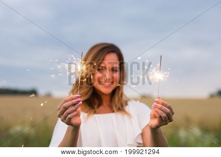Outdoor photo of young beautiful happy smiling girl holding sparkler. Holidays concept