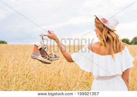 Young woman holding a shoe - sale, consumerism and people concept.