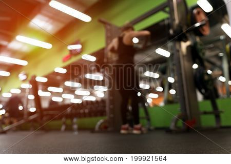 Gym background. Blurred picture of female exercising with barbell in modern fitness center.