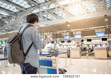 young asian man waiting for check in online by using smartphone and dropping his luggage at airline check-in counter inside the international airport terminal travel lifestyle concept