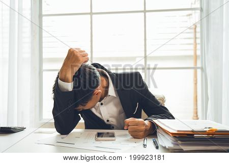 Asian male businessman professional lawyer is tired and migraine headaches during hard work in the attorney general office to fight the court case that will be held next week.