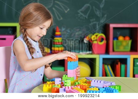 Adorable little girl playing with colorful plastic blocks