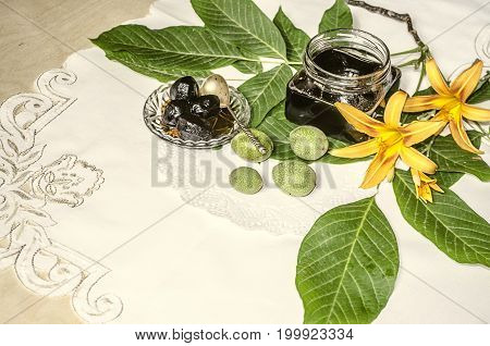 Crystal saucer and glass jar with nut jam near the green walnuts with leaves and orange lilies