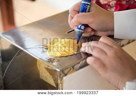 Writing a word into the gold leaf made from bronze.