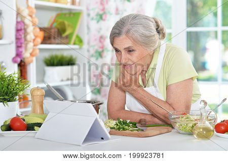 Senior woman reading recipe on laptop while cooking at kitchen