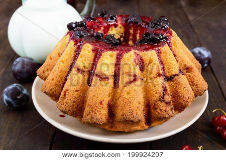 Large freshly baked cake with summer berries on a dark wooden table.
