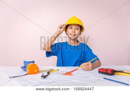 Asian girl child playing as an engineer the building layout and helmet are smiling and happy on weekends.