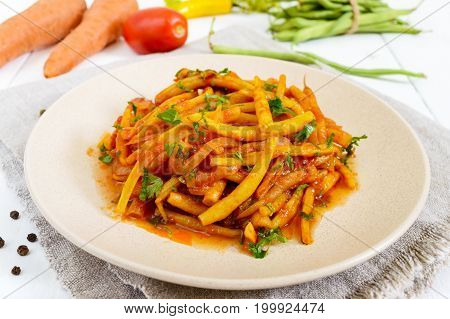 Spicy warm salad of green beans in tomato sauce on a plate on a white wooden background. Vegan dish.
