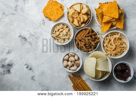 Salty beer snacks in whit bowls, copy space