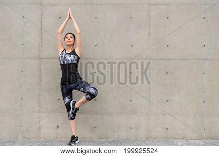 Smiling Elegant Female Jogger Showing Yoga Pose