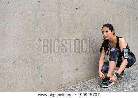Young Seriously Female Jogger Tying Shoelaces