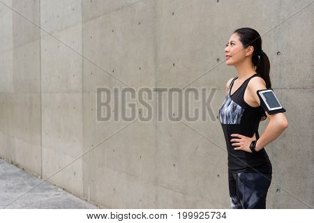Woman Runner Confident Standing On Gray Wall