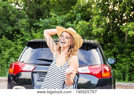 Travel, summer holidays and vacation concept - Young woman with suitcases on car trip