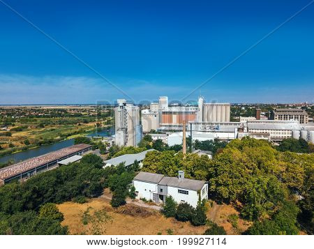 Aerial view of industrial cityscape with factory buildings and warehouses from drone pov