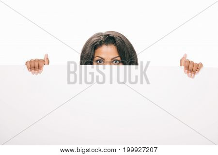 young african american woman peering out blank banner isolated on white