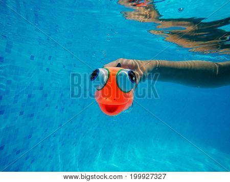 Child playing with generic rubber fish toy in swimming pool summertime activity and enjoyment underwater shot