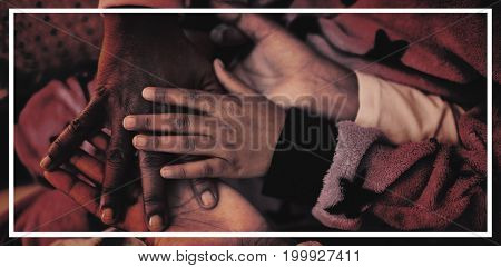 Family forming hand stack while playing on bed in bedroom