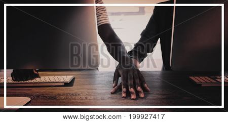 Executives holding hands at their desk in office
