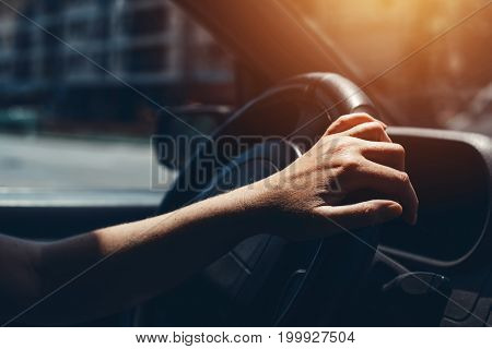 Female hand on car steering wheel woman driving through city streets on sunny summer day