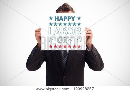 Businessman holding a white card in front of his face against happy labor day text with star shape