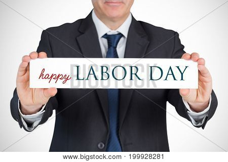 Mature businessman showing card against labor day text