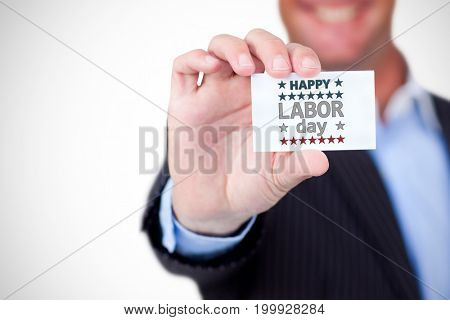 Businessman holding blank card against white background against happy labor day text with star shape