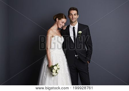 Beautiful bride and groom in studio smiling