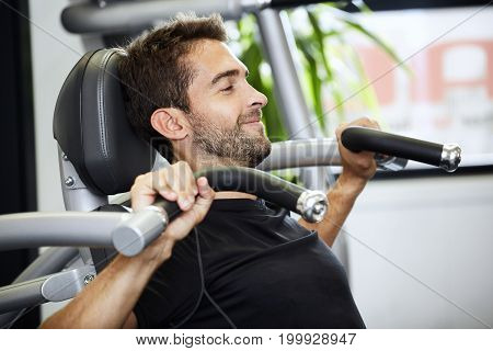 Guy in gym using shoulder press machine smiling