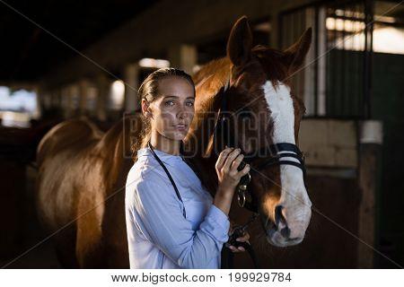 Portrait of female vet stroking horse at stable