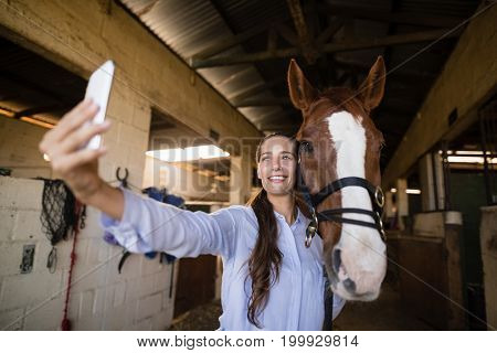 Smiling female vet taking selfie with horse in stable