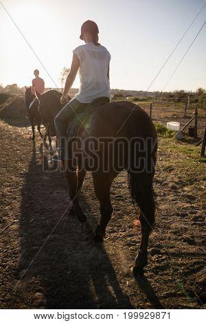 Young women riding horses at barn