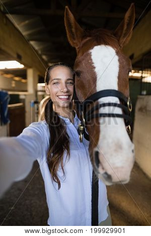 Portrait of female vet standing by horse in stable