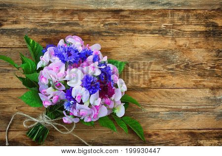 Summer fragrant bouquet of cornflowers and sweet peas on wooden table vintage style copy space