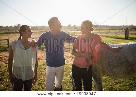Male trainer talking to women while standing by horse at barn
