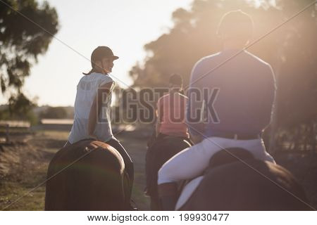 Rear view of trainer with women riding horses at barn during sunny day