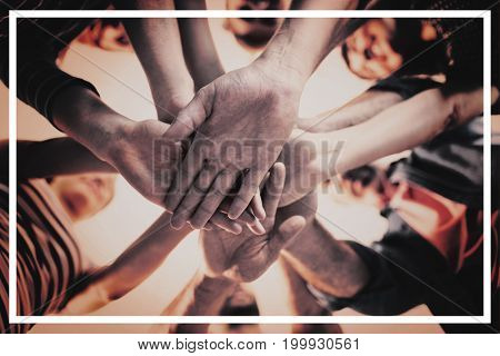 Creative business team stacking hands together in office