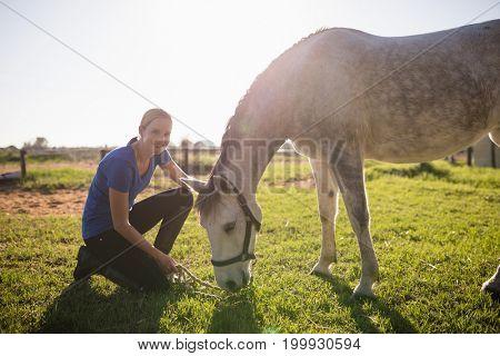 Portrait of smiling jockey stroking horse while kneeling on grassy field