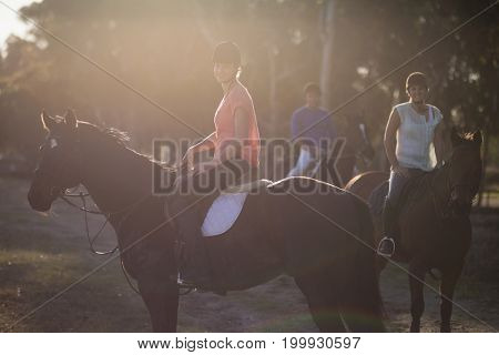 Portrait of trainer with women riding horse at barn