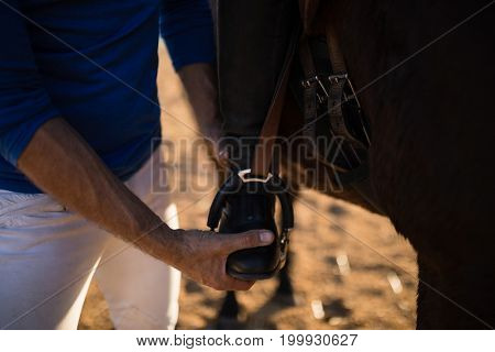 Midsection of male trainer adjusting woman leg on stirrup at barn