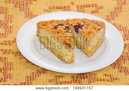 Two pieces of lemon pie with cherry top on a white plate.