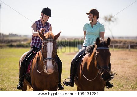 Full length happy female friends talking while horseback riding on field at paddock