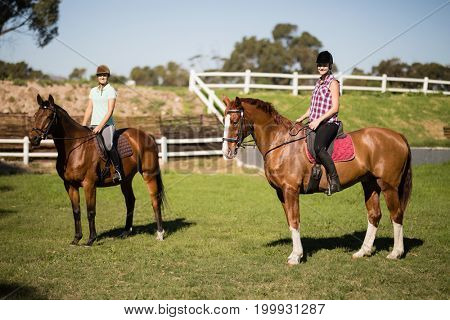 Female friends horseback riding during sunny day at paddock