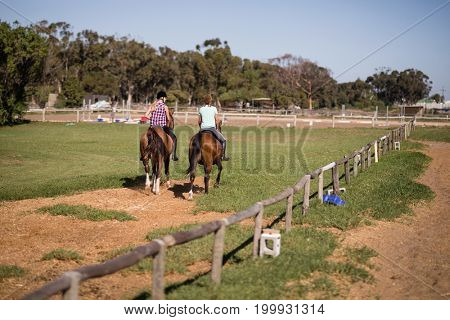 Female friends horseback riding at paddock during sunny day